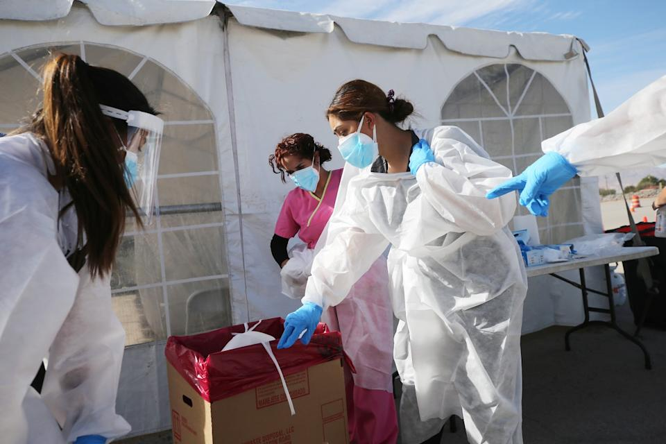 Healthcare workers decontaminate a COVID-19 testing site in El Paso on Friday.