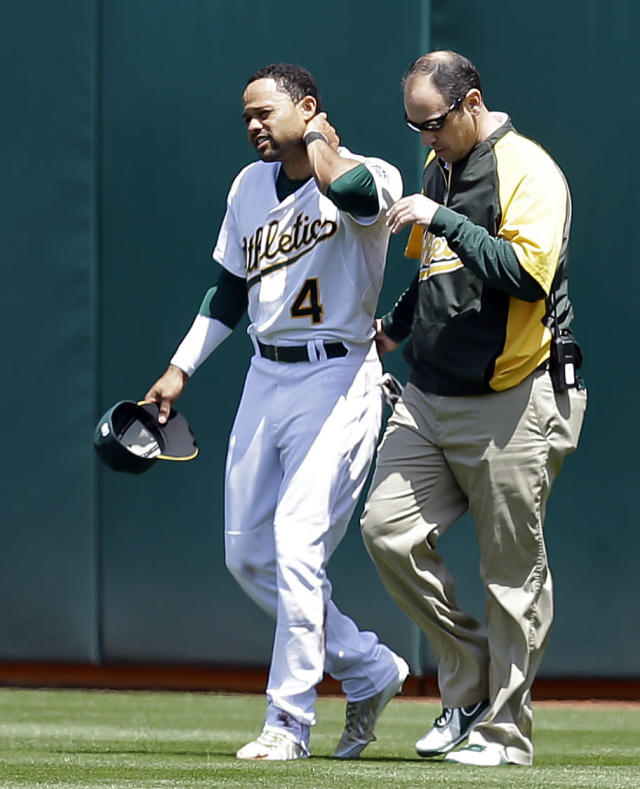 Oakland Athletics' Coco Crisp, left, holds his neck as he walks off the field with head trainer Nick Paparesta in the third inning of a baseball game Wednesday, May 7, 2014, in Oakland, Calif. Crisp injured himself after hitting the wall while catching a ball hit by Seattle Mariners' Kyle Seager. (AP Photo/Ben Margot)