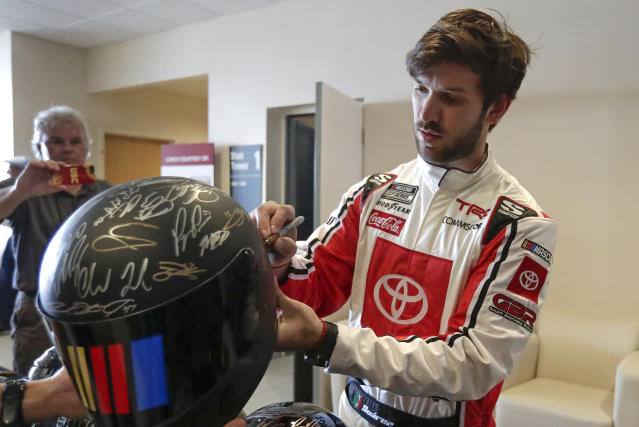 Daniel Suarez autographs a helmet during NASCAR Daytona 500 auto racing media day at Daytona International Speedway, Wednesday, Feb. 12, 2020, in Daytona Beach, Fla. (AP Photo/John Raoux)