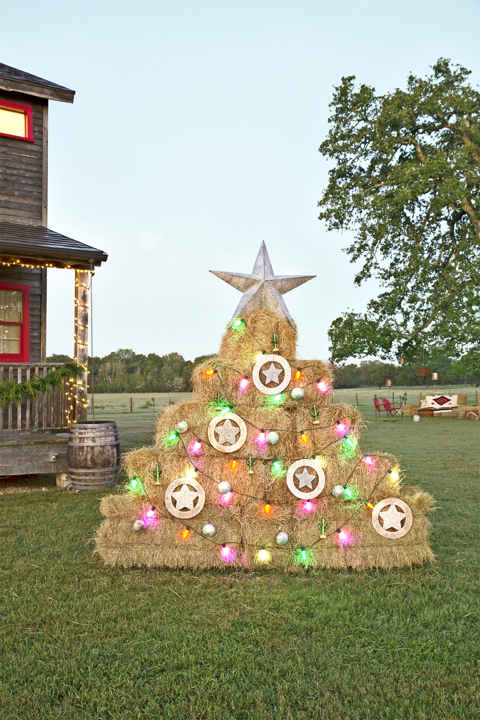 """<p>Draw some inspiration from the Junk Gypsies, who assembled this hay bale Christmas tree outside their <a href=""""https://www.countryliving.com/home-design/house-tours/g4931/junk-gypsies-texas-inn/"""" rel=""""nofollow noopener"""" target=""""_blank"""" data-ylk=""""slk:Wander Inn in Round Top, Texas"""" class=""""link rapid-noclick-resp"""">Wander Inn in Round Top, Texas</a>. Make your own by stacking straw and adorning it with lights, a star, and some ornaments.</p>"""