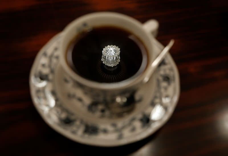 A jewelry-shaped lamp on the ceiling is reflected on a cup of coffee at Shizuo Mori's Heckeln coffee shop in Tokyo