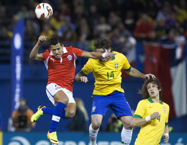Chile's Alexis Sanchez,left, competes for the ball with Brazil's Maxwell, center, as David Luiz watches during first half action of their international friendly match in Toronto on Tuesday, Nov. 19, 2013. (AP Photo/The Canadian Press, Chris Young)