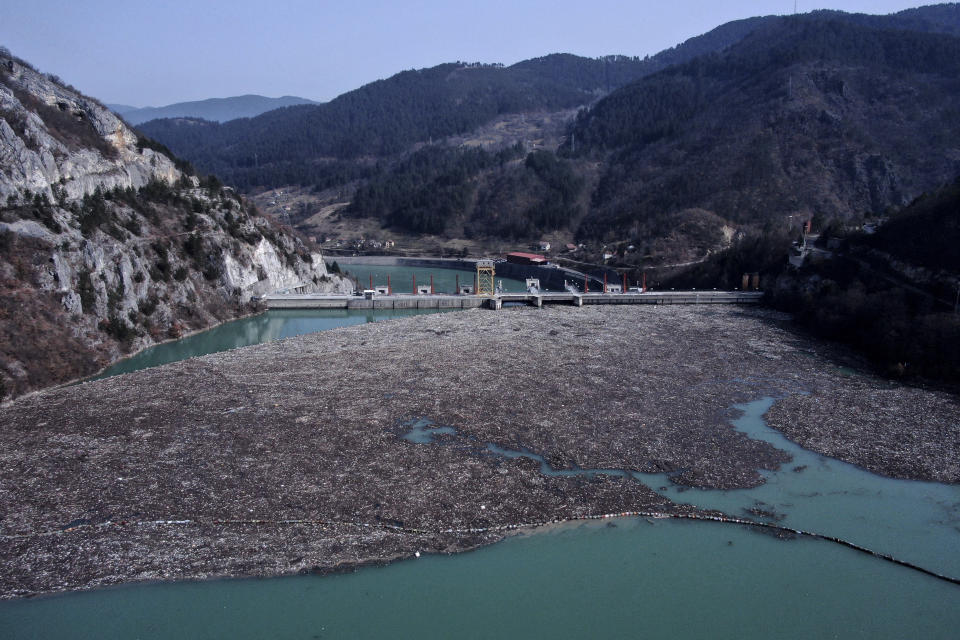 This aerial photo shows a dam garbage floating in the Drina river near Visegrad, eastern Bosnia, Wednesday, Feb. 24, 2021. Environmental activists in Bosnia are warning that tons of garbage floating down the Balkan country's rivers are endangering the local ecosystem and people's health. The Drina River has been covered for weeks with trash that has piled up faster than the authorities can clear it out. (AP Photo/Kemal Softic)