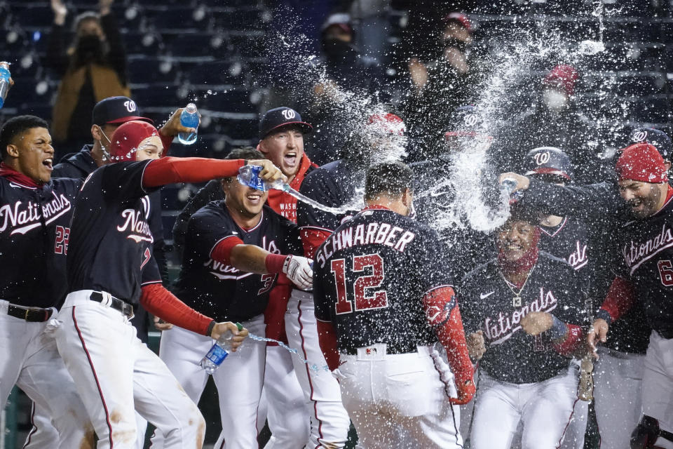 Washington Nationals' Kyle Schwarber (12) celebrates his game-winning home run during the ninth inning of a baseball game against the Arizona Diamondbacks at Nationals Park, Friday, April 16, 2021, in Washington. The Nationals won 1-0. (AP Photo/Alex Brandon)