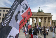 A protestor holds a flag of the German Reich with a picture of US President Donald Trump in front of the Brandenburg Gate before a demonstration against the coronavirus measures by the German Government in Berlin, Germany, Saturday, Aug. 29, 2020. (Christophe Gateau/dpa via AP)