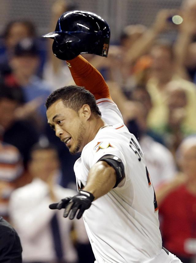 Miami Marlins' Giancarlo Stanton runs to home plate after hitting a grand slam to defeat the Seattle Mariners 8-4 during the ninth inning of an interleague baseball game, Friday, April 18, 2014, in Miami. (AP Photo/Lynne Sladky)