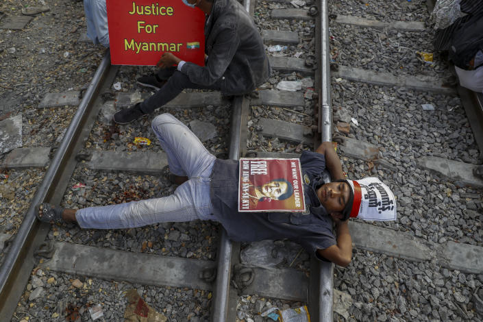 Demonstrators with placards lie on the railway tracks in an attempt to disrupt train service during a protest against the military coup in Mandalay, Myanmar on Wednesday, Feb. 17, 2021. Demonstrators in Myanmar gathered Wednesday in their largest numbers so far to protest the military's seizure of power, even after a U.N. human rights expert warned that troops being brought to Yangon and elsewhere could signal the prospect of major violence. (AP Photo)