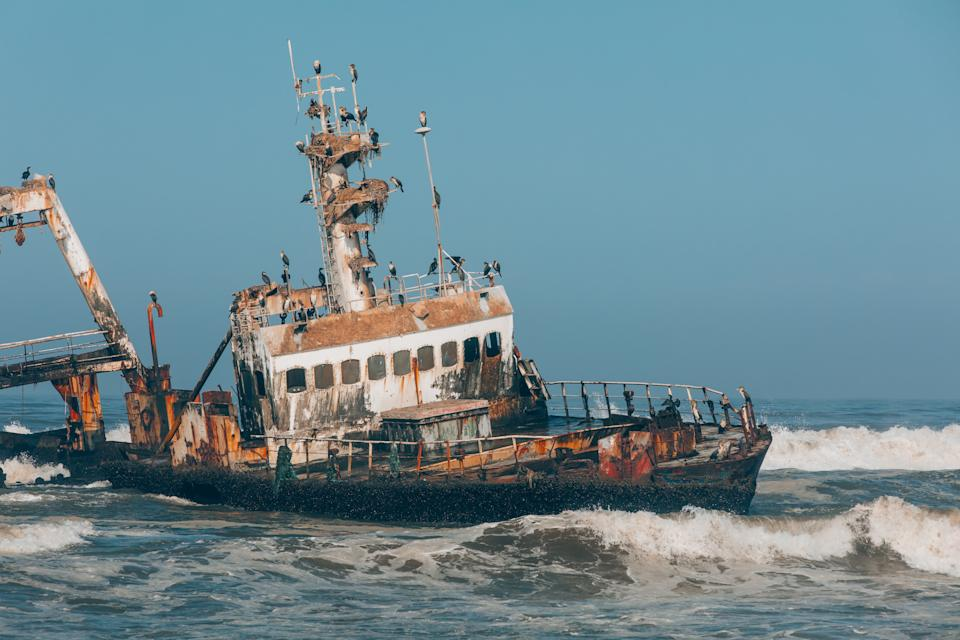 Abandoned and derelict old shipwreck Zeila at the Atlantic Coast near Swakopmund and Henties Bay, famous Skeleton Coast in Namibia, Africa. Group of cormorants birds perching on rusted ship.