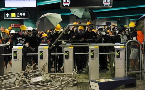 Protesters use steels barricades to form a defensive line inside the Quarry bay MTR station - Credit: AP