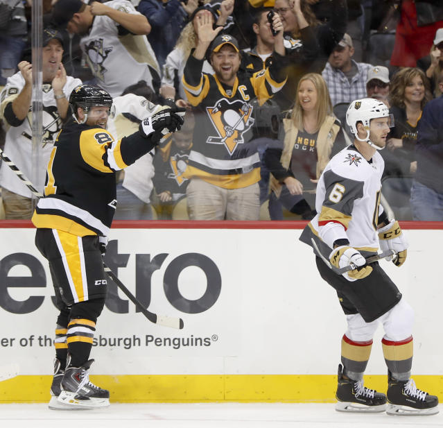 Pittsburgh Penguins' Phil Kessel, left, celebrates behind Vegas Golden Knights' Colin Miller after scoring his first goal during the second period, and second goal of an NHL hockey game, Thursday, Oct. 11, 2018, in Pittsburgh. (AP Photo/Keith Srakocic)