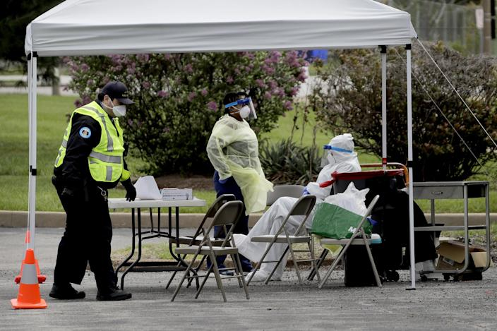 Health care workers and security personnel wait for patients at a drive-up COVID-19 testing location on Monday, where the coronavirus outbreak is taking a disproportionate toll in a predominately black area of St. Louis.