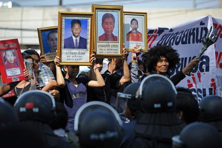 Protesters hold up pictures of some of those killed during May 2010 crackdown in Bangkok, on December 13, 2012