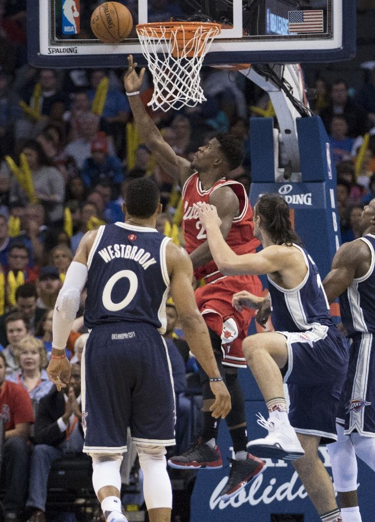 Jimmy Butler (C) of the Chicago Bulls slides between Russell Westbrook (L) and Steven Adams of the Oklahoma City Thunder for two points during the third quarter of a NBA game at the Chesapeake Energy Arena on December 25, 2015 in Oklahoma City (AFP Photo/J Pat Carter)