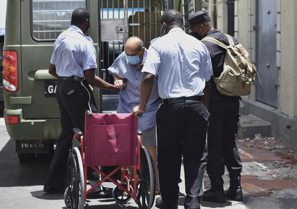 Antigua and Barbuda businessman Mehul Choksi is helped into a wheelchair by police as he arrives to the magistrate's court in Roseau, Dominica, Friday, June 4, 2021. Choksi is wanted in his native India on a string of charges that include corruption, money laundering and criminal conspiracy. The fugitive was arrested May 24 on the neighboring island of Dominica accused of illegal entry. (AP Photo/Clyde Jno Baptiste)