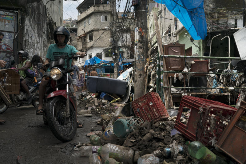 A man rides his motorcycle through an alley strewn with debris and mud in the aftermath of a violent storm in the Rocinha slum, in Rio de Janeiro, Brazil, Thursday, Feb. 7, 2019. Rio officials say torrential downpours and strong winds have killed at least five people and left a trail of destruction. (AP Photo/Leo Correa)
