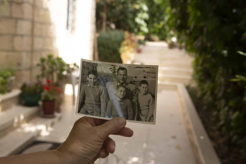 Samira Dajani holds a photo of her father, Fouad Moussa Dajani and his sons, taken in the same place in the courtyard of their home in the Sheikh Jarrah neighborhood of east Jerusalem, Sunday, May 9, 2021. When Samira Dajani's family moved into their first real home in 1956 after years as refugees, her father planted trees in the garden, naming them for each of his six children. (AP Photo/Maya Alleruzzo)