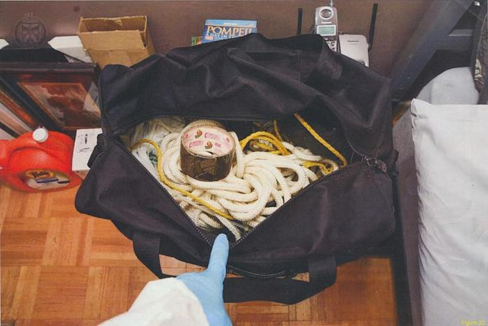 <p>Police found this black duffel bag containing duct tape, a surgical glove, rope, zip ties, a black bungee cord and syringes in McArthur's bedroom. (Photo provided by the Crown) </p>