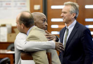 Dewayne Johnson, center, hugs one of his attorneys, next to lawyer and member of his legal team Robert F Kennedy Jr., right, after the verdict was read in his case against Monsanto at the Superior Court of California in San Francisco on Friday, Aug. 10, 2018. A San Francisco jury on Friday ordered agribusiness giant Monsanto to pay $289 million to the former school groundskeeper dying of cancer, saying the company's popular Roundup weed killer contributed to his disease. (Josh Edelson/Pool Photo via AP)