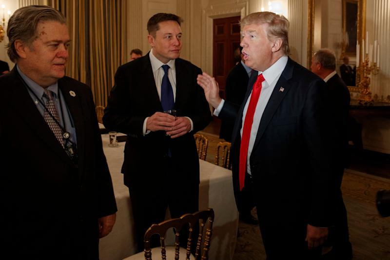President Donald Trump talks with Tesla and SpaceX CEO Elon Musk, center, and White House chief strategist Steve Bannon during a meeting with business leaders in the State Dining Room of the White House in Washington on Friday, Feb. 3, 2017.