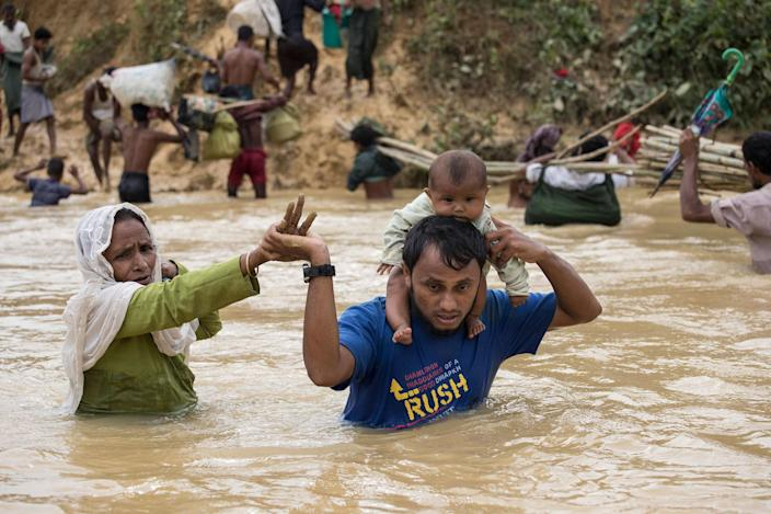 <p>Rohingya desperately try to cross a river on a crowded makeshift bamboo bridge at Kutpalong camp on September 20, 2017. (Photograph by Paula Bronstein/UNHCR) </p>