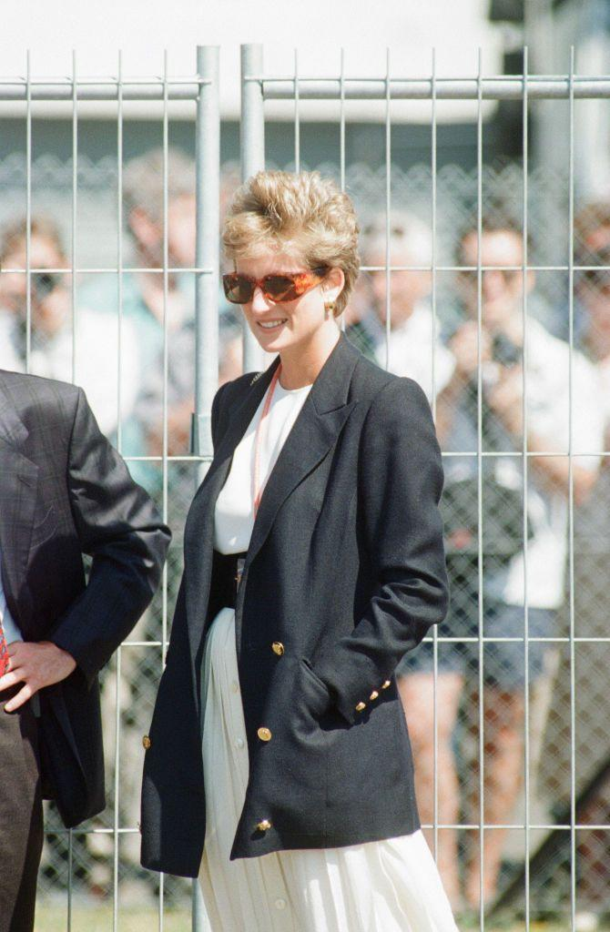 <p>Princess Diana wore a belted ivory skirt and white blouse, which she accessorized with an oversized black blazer to the 1994 British Grand Prix. </p>