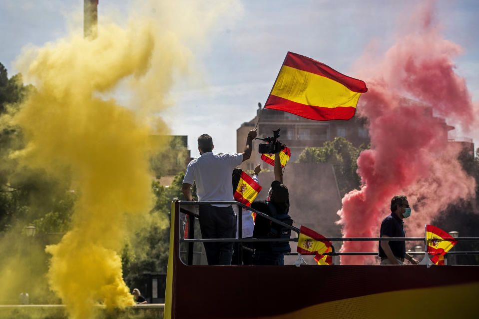 People wave Spanish flags as they burn flares during a drive-in protest organised by Spain's far-right Vox pazrty against the Spanish government's handling of the nation's coronavirus outbreak in Madrid, Spain Saturday, May 23, 2020. (AP Photo/Manu Fernandez)