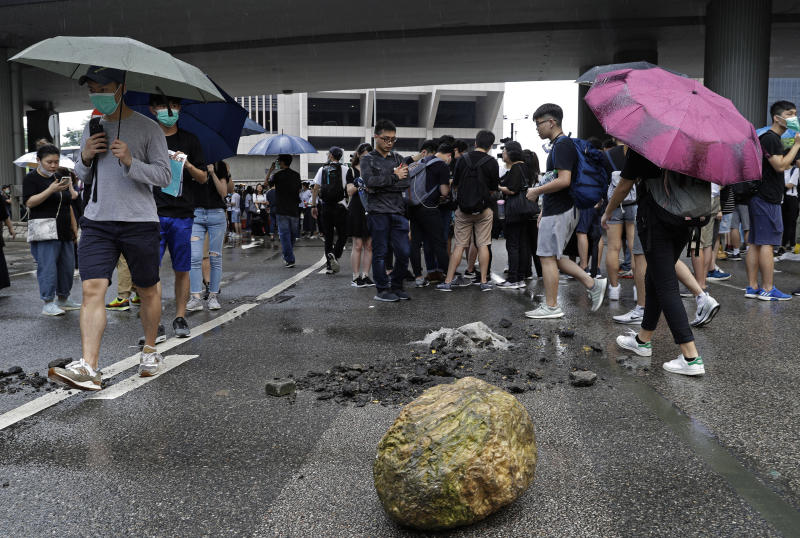 A big rock has been placed in the road as protesters gather outside the Legislative Council in Hong Kong, Wednesday, June 12, 2019. Hundreds of protesters have blocked access to Hong Kong's legislature and government headquarters in a bid to block debate on a highly controversial extradition bill that would allow accused people to be sent to China for trial. (AP Photo/Vincent Yu)