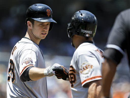 San Francisco Giants' Buster Posey, left, knocks knuckles with Andres Torres after Torres scored against the San Diego Padres in the first inning of a baseball game in San Diego, Sunday, July 14, 2013. (AP Photo/Lenny Ignelzi)