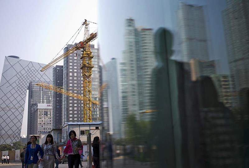 FILE - In this Oct. 8, 2013 file photo, Chinese people walk past a construction site and office buildings, which are reflected on window glass at the Central Business District in Beijing, China. Growth has marched steadily downward over the past two years as Beijing clamped down on a spending boom that analysts worry has pushed debt to dangerous levels. (AP Photo/Andy Wong, File)
