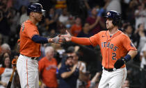 Houston Astros' Alex Bregman, right, celebrates with with Carlos Correa after scoring a run on Yordan Alvarez's RBI-double during the third inning of a baseball game against the Los Angeles Angels, Friday, Sept. 10, 2021, in Houston. (AP Photo/Eric Christian Smith)