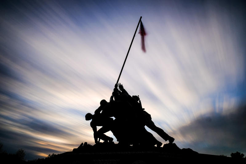 The sun sets behind the U.S. Marine Corps War Memorial in Arlington, Va., Sunday, Nov. 10, 2019, in this slow-shutter speed exposure. Veterans Day will be celebrated in the United States on Monday. (AP Photo/J. David Ake)
