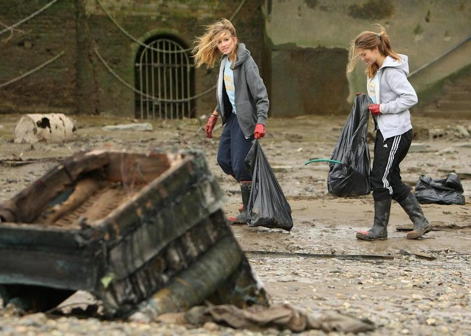 Members of Surfers Against Sewage and Thames 21 clean the banks of the river Thames, near Battersea Bridge in south west London, as part of the Surfers Against Sewage 20th anniversary Beach Clean Tour, which has visited 20 major UK beaches and waterside locations (Dominic Lipinski/PA) (PA Archive)