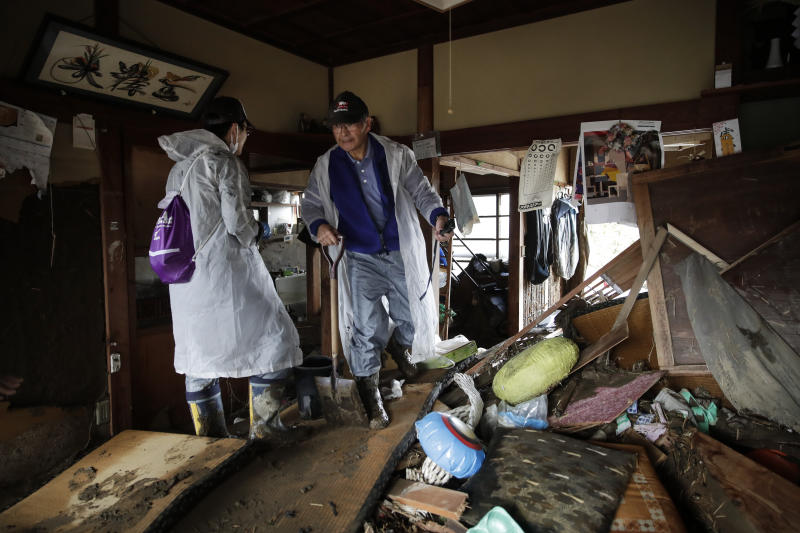Toshio Yonezawa, 73, center, surveys his home with son, Yusuke, after Typhoon Hagibis passed through his neighborhood, Oct. 15, 2019, in Nagano, Japan. (Photo: Jae C. Hong/AP)