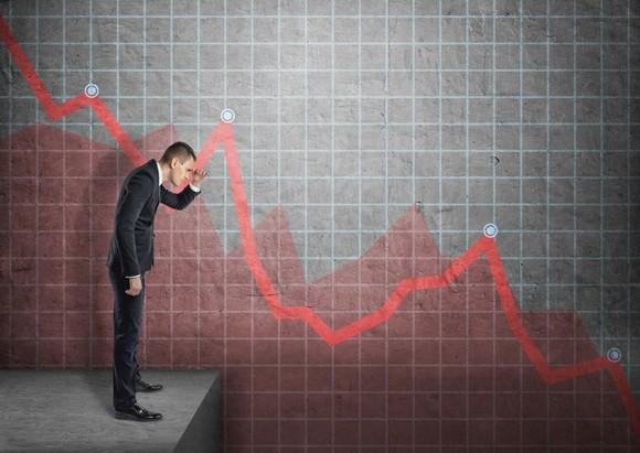 A businessman watches a plunging stock chart.