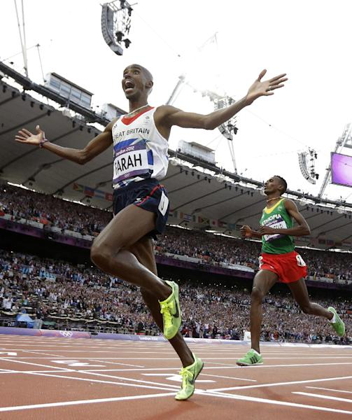 Britain's Mo Farah reacts as he crosses the finish line to win gold in the men's 5000-meter final ahead of Ethiopia's Dejen Gebremeskel during the athletics in the Olympic Stadium at the 2012 Summer Olympics, London, Saturday, Aug. 11, 2012. (AP Photo/David J. Phillip)