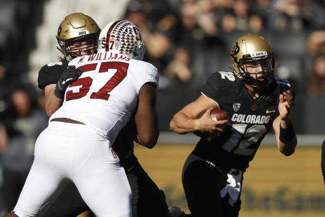Stanford defensive tackle Michael Williams, front left, is stopped by Colorado offensive lineman Kary Kutsch, back left, as quarterback Steven Montez runs for a short gain in the first half of an NCAA college football game Saturday, Nov. 9, 2019, in Boulder, Colo. (AP Photo/David Zalubowski)