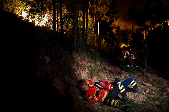 <p>Firefighters rest during a forest fire at Penela, Coimbra, central Portugal, on June 18, 2017. (Patricia De Melo Moreira/AFP/Getty Images) </p>