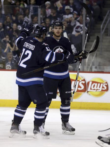 Winnipeg Jets' Drew Stafford (12) celebrates with Adam Lowry (17) after Lowry scored against the Minnesota Wild during the second period of an NHL hockey game Tuesday, Feb. 28, 2017, in Winnipeg, Manitoba. (Trevor Hagan/The Canadian Press via AP)