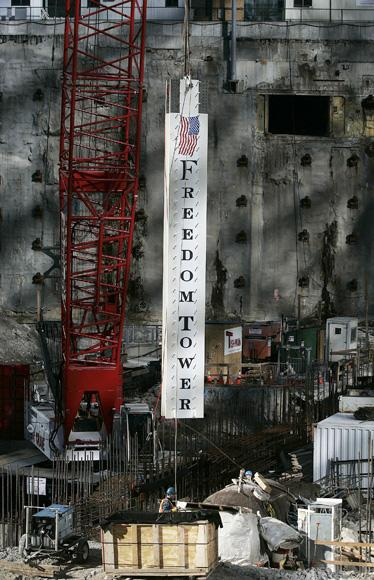 NEW YORK - DECEMBER 19:  A commemorative steel beam is lowered into place at the site of the Freedom Tower at Ground Zero December 19, 2006 in New York City.  Several 25-ton steel beams were erected with fanfare at Ground Zero, marking the first vertical construction of the planned 1,776 foot tower at the site of the Twin Towers.  (Photo by Chris Hondros/Getty Images)