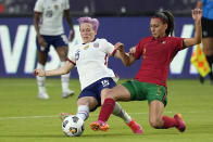 United States' Megan Rapinoe (15) and Portugal's Catarina Amado (2) slide for the ball during the first half of an international friendly soccer match Thursday, June 10, 2021, in Houston. (AP Photo/David J. Phillip)