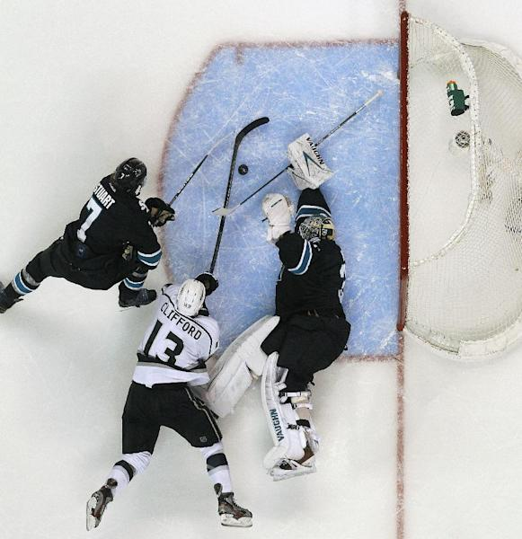 San Jose Sharks goalie Antti Niemi (31), of Finland, blocks a goal attempt by Los Angeles Kings left wing Kyle Clifford (13) as Sharks defenseman Brad Stuart (7) defends during the second period in Game 6 of their second-round NHL hockey Stanley Cup playoff series in San Jose, Calif., Sunday, May 26, 2013. (AP Photo/Tony Avelar)