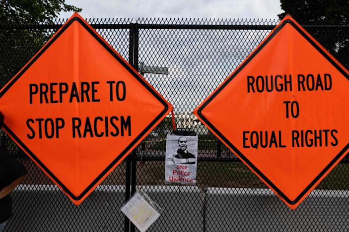 Placards placed by protesters hang from a fence erected in front of Lafayette Park near the White House in June.