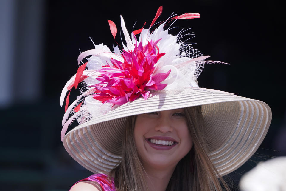 A woman watches a race before the 147th running of the Kentucky Derby at Churchill Downs, Saturday, May 1, 2021, in Louisville, Ky. (AP Photo/Michael Conroy)