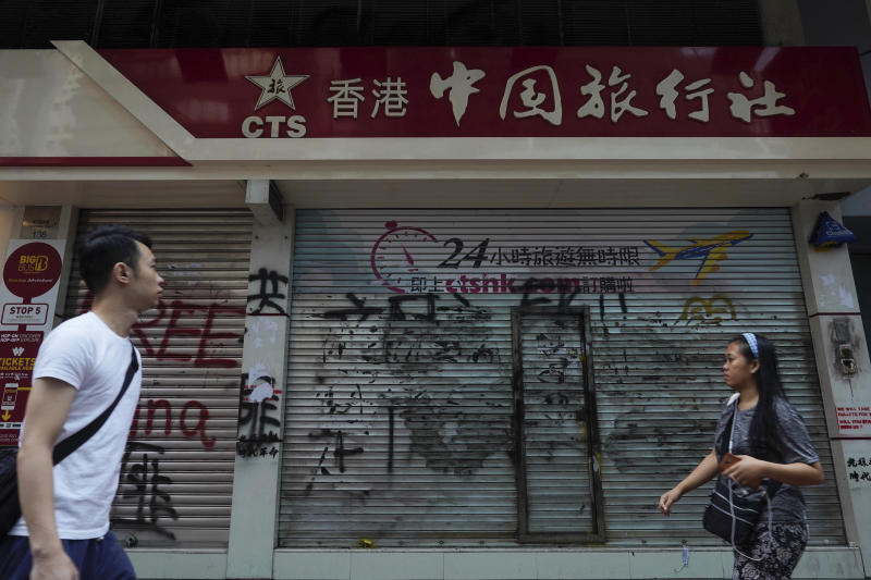 FILE - In this Oct. 7, 2019, file photo, pedestrians look at graffiti in front of China Travel Service in Hong Kong. Hong Kong's embattled leader Carrie Lam said Tuesday that the city's economy is being battered by months of increasingly violent protests. (AP Photo/Vincent Yu, File)