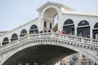 People visit the Rialto bridge in Venice, northern Italy, Saturday, May 1, 2021. Italy is gradually reopening after six months of rotating virus closures allowing outdoor dining. (Filippo Ciappi/LaPresse via AP)