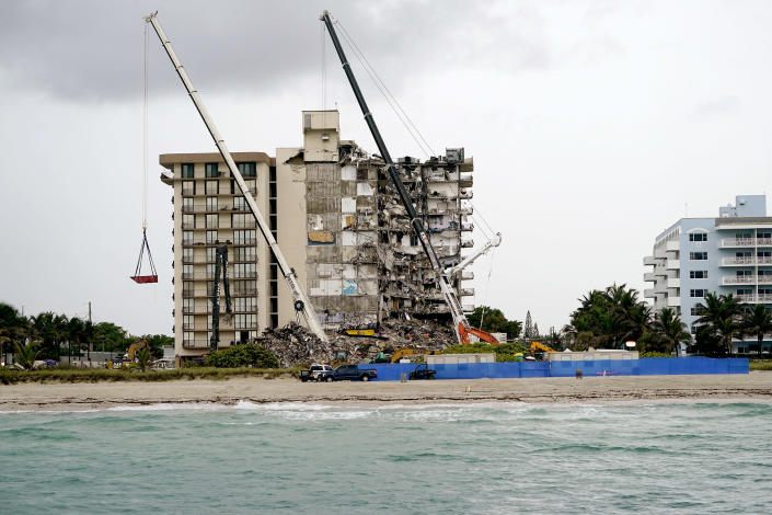 Image: Search and rescue personnel work alongside heavy machinery to sift through the rubble at the Champlain Towers South condo building, where scores of people remain missing almost a week after it partially collapsed on June 30, 2021, in Surfside, Fla. (Lynne Sladky / AP)
