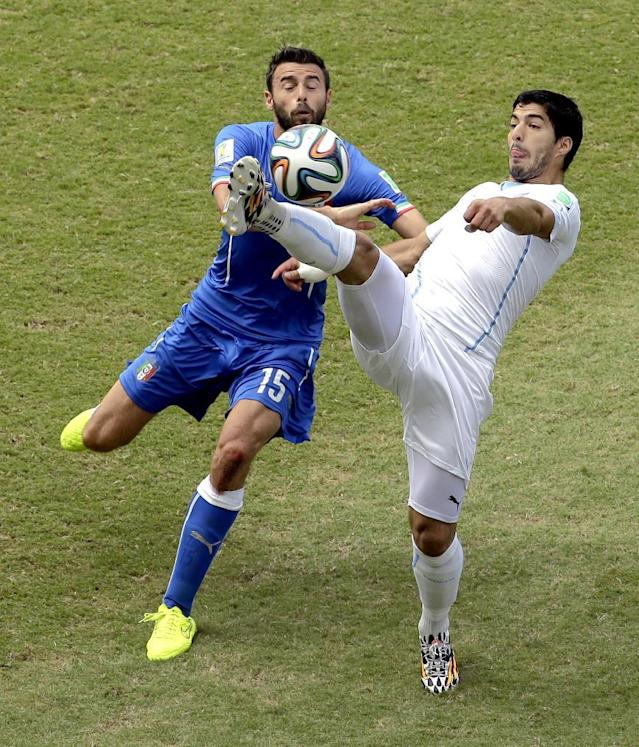 Uruguay's Luis Suarez, right, and Italy's Andrea Barzagli (15) challenge for the ball during the group D World Cup soccer match between Italy and Uruguay at the Arena das Dunas in Natal, Brazil, Tuesday, June 24, 2014. (AP Photo/Hassan Ammar)