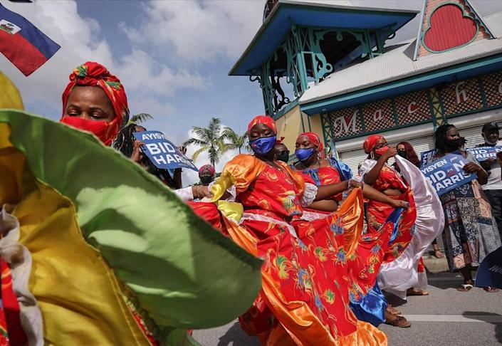 Nancy St. Leger, left, and her NSL Danse Ensemble spill their performance into NE 2nd Avenue outside the Little Haiti Cultural Complex's Caribbean Marketplace as Haitian American supporters of Democratic presidential nominee Joe Biden lined the streets of Northeast Second Avenue in Little Haiti hoping to catch a glimpse of the visit of the candidate as he arrived at the Little Haiti Cultural Center on Monday, October 5, 2020.