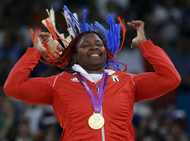 Cuba's Idalys Ortiz reacts after receiving her gold medal for the women's over 78-kg judo competition at the 2012 Summer Olympics, Friday, Aug. 3, 2012, in London. (AP Photo/Paul Sancya)
