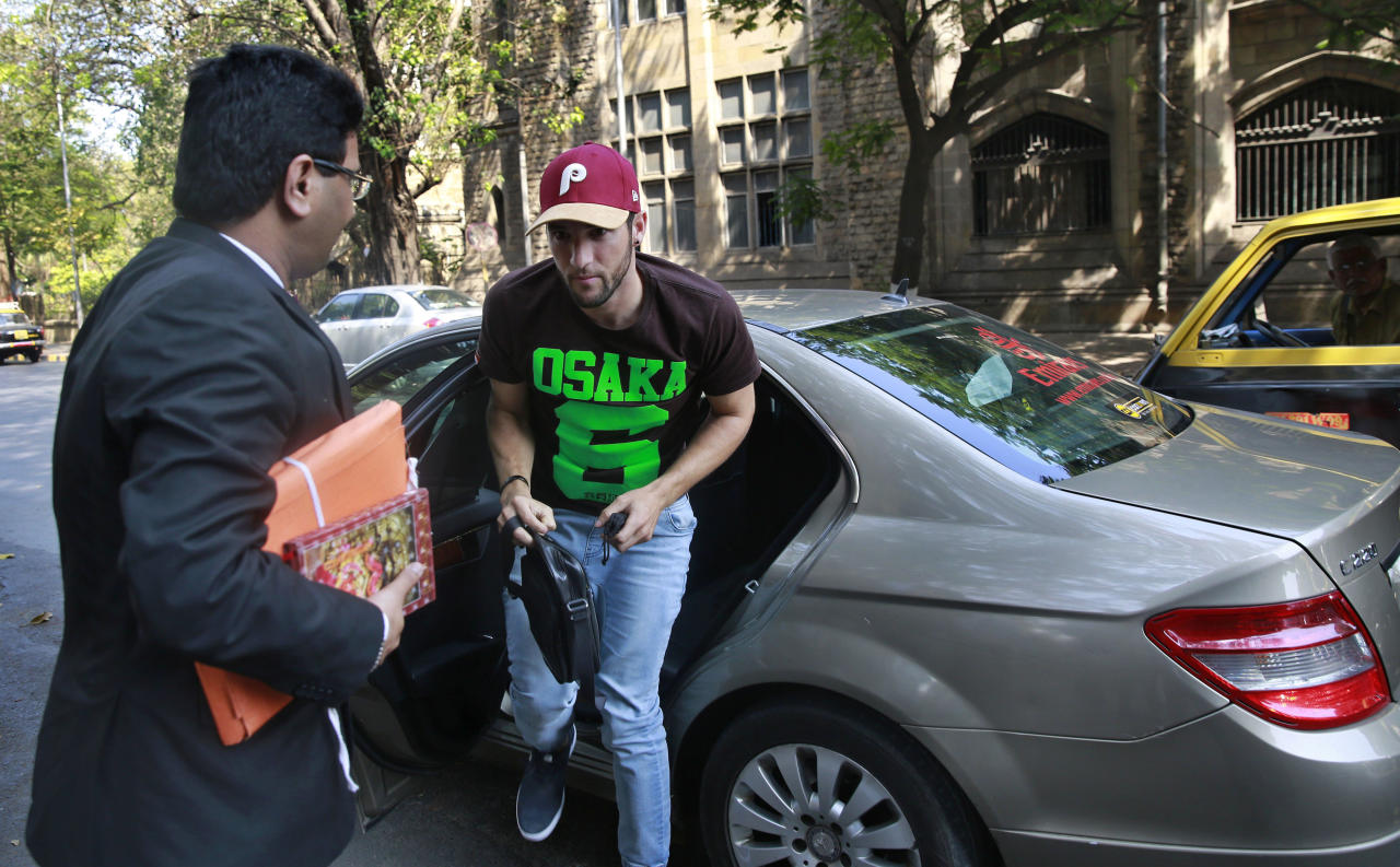 South African cricket player Wayne Parnell, center, gets out of a car as he arrives to appear in a court over a drug-related charge handed to him during the 2012 Indian Premier League in Mumbai, India, Thursday, March 27, 2014. Parnell has been omitted from the South Africa squad for its Thursday's World Twenty 20 match against the Netherlands to enable the court appearance. (AP Photo/Rafiq Maqbool)